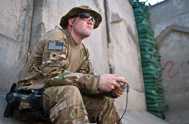 U.S. Army Spc. Andrew B. Clement, an explosive ordnance disposal technician assigned to 129th EOD, attached to 3rd Brigade Combat Team, 25th Infantry Division, Task Force Bronco, uses an Xbox controller and a computer viewfinder to maneuver an EOD robot at Combat Outpost Honaker-Miracle in eastern Afghanistan's Kunar province, on August 1, 2012. (Photo by Sgt. 1st Class Mark Burrell/U.S. Army)