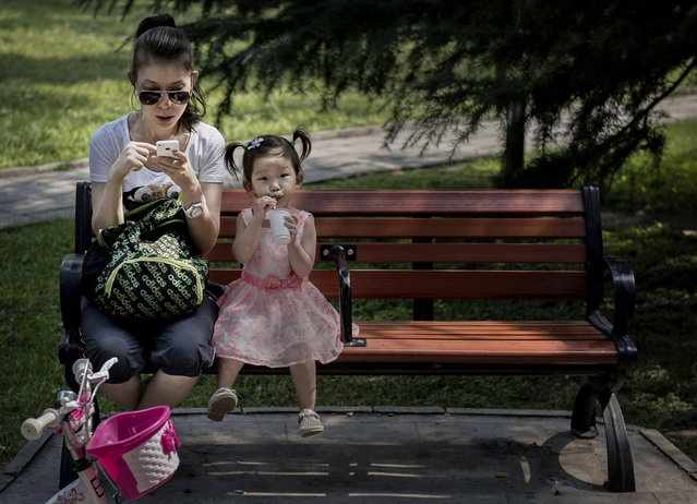 A Chinese woman uses her smartphone as her daughter sits beside her on a park bench on September 10, 2014 in Beijing, China. China tightened censorship on mobile messaging apps last month and blocked a number of foreign chat services, according to media reports. (Photo by Kevin Frayer/Getty Images)