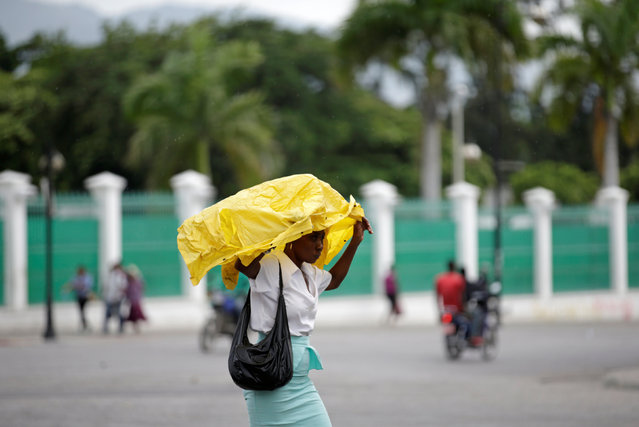 A woman covers herself with a raincoat to protect from light rain as she walks in Port-au-Prince, Haiti, August 1, 2016. (Photo by Andres Martinez Casares/Reuters)