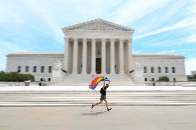 Joseph Fons holding a Pride Flag, runs in front of the U.S. Supreme Court building after the court ruled that a federal law banning workplace discrimination also covers sexual orientation, in Washington, D.C., U.S., June 15, 2020. (Photo by Tom Brenner/Reuters)