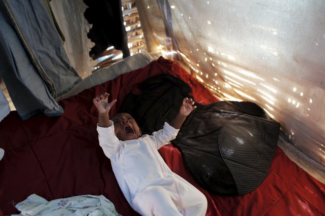Lisania Disten yawns while resting on a bed inside a makeshift tent at a refugee camp for Haitians returning from the Dominican Republic and where she lives with her family on the outskirts of Anse-a-Pitres, Haiti, September 7, 2015. (Photo by Andres Martinez Casares/Reuters)