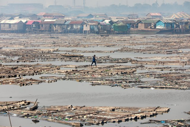 A man walks on logs of wood placed on the river at the Makoko community in Lagos, Nigeria on March 9, 2020. (Photo by Temilade Adelaja/Reuters)
