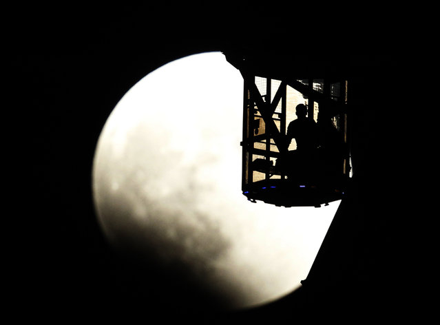 The Earth's shadow renders the moon as a couple in Ferris wheel observe it during a total lunar eclipse in Tokyo, Wednesday, October 8, 2014. (Photo by Koji Sasahara/AP Photo)