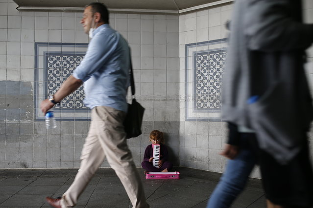 People, some wearing protective masks against the spread of coronavirus, walk by a child playing music for money on an underpass in Istanbul, Thursday, June 18, 2020. (Photo by Emrah Gurel/AP Photo)