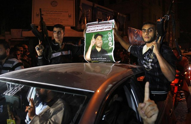 Palestinian gunmen hold a poster of late Ahmed Jabari, head of the Hamas military wing in Gaza City, while they celebrate the cease-fire agreement between Israel and Hamas in Gaza City, Wednesday, November 21, 2012. Israel and the Hamas militant group agreed to a cease-fire Wednesday to end eight days of the fiercest fighting in nearly four years, promising to halt attacks on each other and ease an Israeli blockade constricting the Gaza Strip. (Photo by Adel Hana/AP)