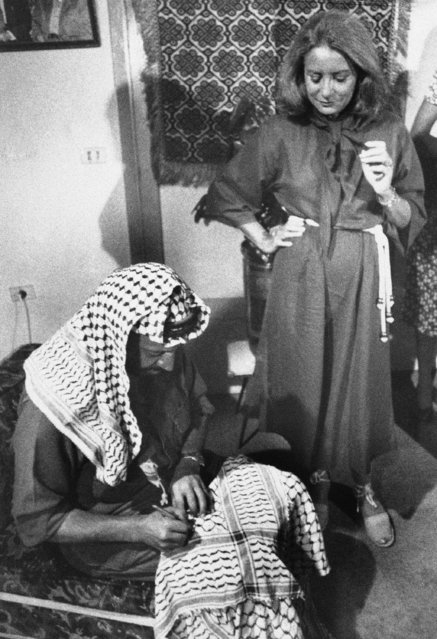 Barbara Walters of ABC-TV watches over Palestinian guerrilla leader Yasir Arafat as he autographs a keffiyeh, an Arab headdress, after she interviewed him in Beirut, September 21 1987. (Photo by Harry Koundakjian/AP Photo)