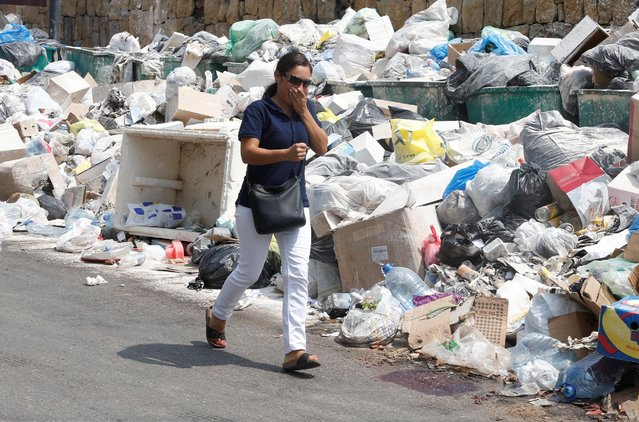 A woman covers her nose as she walks past garbage piled up along a street in Dekwaneh area, Mount Lebanon August 29, 2016. (Photo by Mohamed Azakir/Reuters)