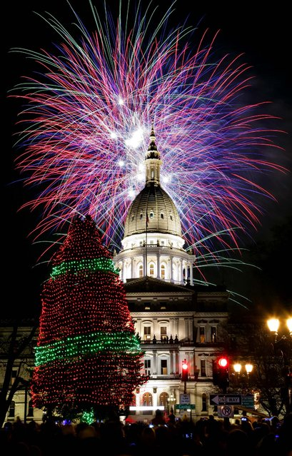 Fireworks explode over the state Capitol following the ceremonial lighting of the official state Christmas tree in Lansing, Michigan. (Photo by Al Goldis/Associated Press)