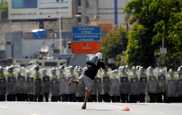 A protester throws a stone while taking part in a rally to demand a referendum to remove Venezuela's President Nicolas Maduro in Caracas, Venezuela, September 1, 2016. (Photo by Christian Veron/Reuters)