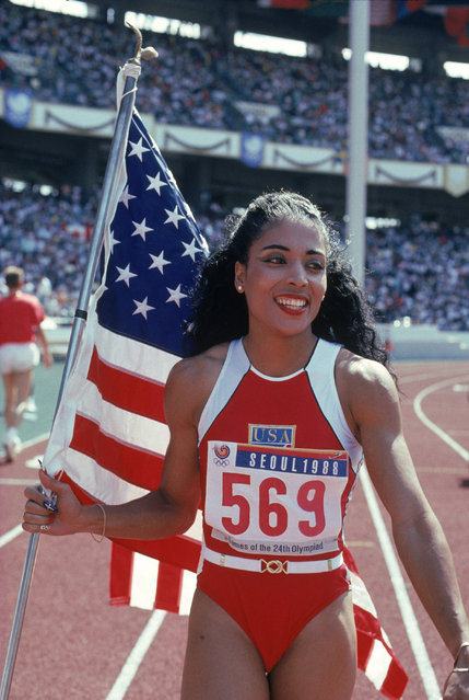 Florence Griffith Joyner of the USA walks with the American Flag as she celebrates setting a new Olympic record to win the gold medal in the Women's 100 meters dash final during the 1988 Summer Olympic Games on September 28, 1988 in Seoul, Korea. (Photo by Tony Duffy/Getty Images)