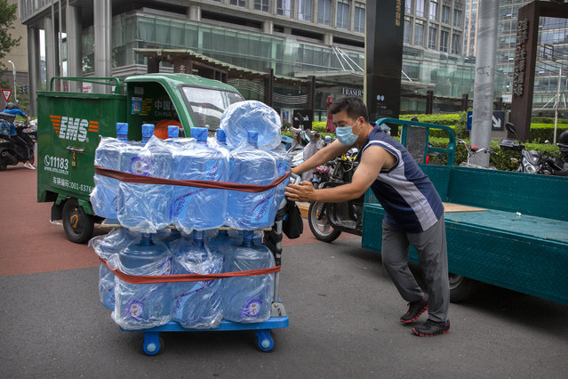 A worker wearing a face mask to protect against the coronavirus pushes a cart loaded with bottles of drinking water in Beijing, Friday, July 17, 2020. Further restrictions are being imposed on the northwestern Chinese city of Urumqi following a cluster of new cases. (Photo by Mark Schiefelbein/AP Photo)