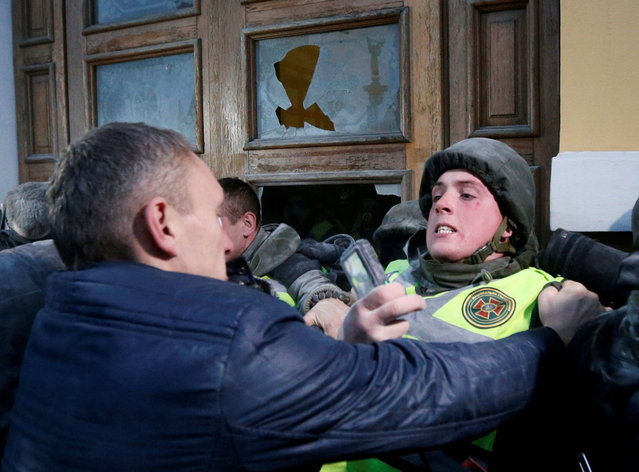 Supporters of former Georgian President and Ukrainian opposition figure Mikheil Saakashvili clash with police as they try to break into the building of the International Art Centre in Kiev, Ukraine, December 17, 2017. (Photo by Valentyn Ogirenko/Reuters)