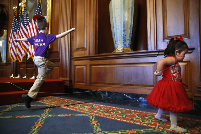 Jack Nelson, 6, of Manassas, Va., left, who has cystic fibrosis, leaps over the oxygen tubing of Melanie Carrigg, 5, who has Down syndrome, is deaf, and has Glycogen Storage Disease, before a news conference with House Minority Leader Nancy Pelosi of Calif., in opposition to the Republican tax bill, Tuesday, December 19, 2017, on Capitol Hill in Washington. Jack's parents depend on the orphan drug tax credit and are concerned about it's reduction in the Republican plan. (Photo by Jacquelyn Martin/AP Photo)