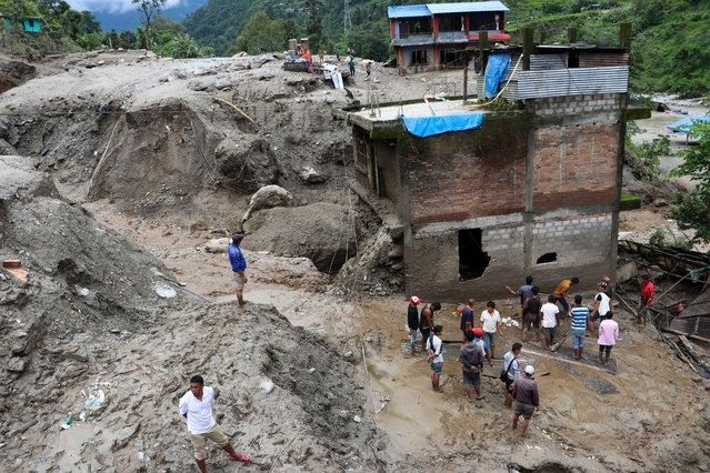 Residents and rescue workers inspect the area outside a house damaged by a landslide and the swell of the Thado-Koshi river due to heavy rains in Jambu village of Sindhupalchok district, some 80 kms northeast of Kathmandu on July 9, 2020. Two people died and several others have gone missing, local media reported. (Photo by Niroj Chaoulagain/AFP Photo)