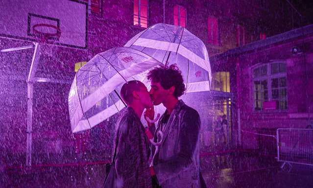 "A couple share a kiss at the ""Purple Rain"" installation at the Lycée Jacques-Decour on August 02, 2020 in Paris, France. Part of Festival Paris l'Eté, the installation by Pierre Ardouvin is a tribute to the song by Prince and allows visitors to role play while equipped with umbrellas and accompanied by the song. (Photo by Kiran Ridley/Getty Images)"