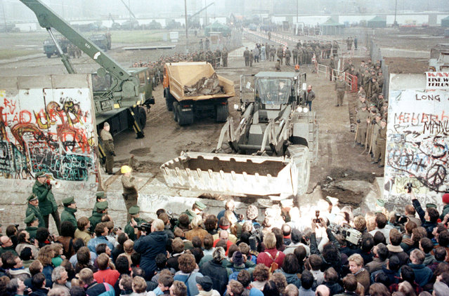 An East German bulldozer and crane knock down the Berlin Wall at Potsdamer Platz to make way for a new border crossing in the dvided city, November 12, 1989. (Photo by Reuters)