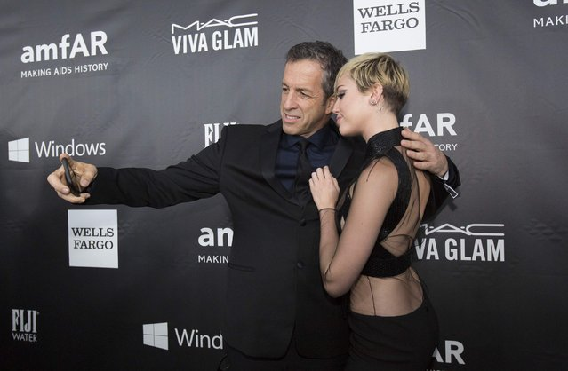 Fashion designer Kenneth Cole takes a selfie with singer Miley Cyrus at the amfAR's Fifth Annual Inspiration Gala in Los Angeles, California October 29, 2014. (Photo by Mario Anzuoni/Reuters)