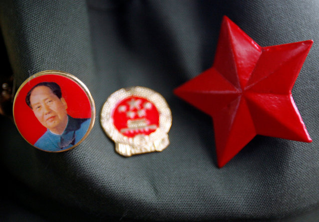 A badge bearing the portrait of former Chinese Chairman Mao Zedong can be seen attached to a hat next to a Chinese Communist Party badge and a red star at a market in Beijing July 1, 2008. (Photo by David Gray/Reuters)