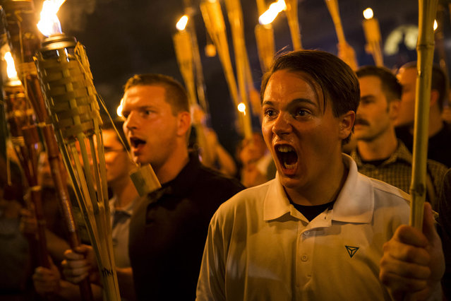 Peter Cvjetanovic (R) along with Neo Nazis, Alt-Right, and White Supremacists encircle and chant at counter protestors at the base of a statue of Thomas Jefferson after marching through the University of Virginia campus with torches in Charlottesville, Va. on August 11, 2017. (Photo by Samuel Corum/Anadolu Agency/Getty Images)
