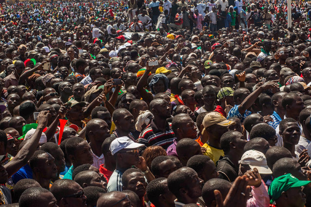 People gather near a government building as they await the announcement of a new interim leader in Ouagadougou, Burkina Faso, Friday, October 31, 2014. An army general stepped into the vacuum left in Burkina Faso on Friday by the resignation President Blaise Compaore, who ended his 27-year reign under pressure from violent protests. (Photo by Theo Renaut/AP Photo)