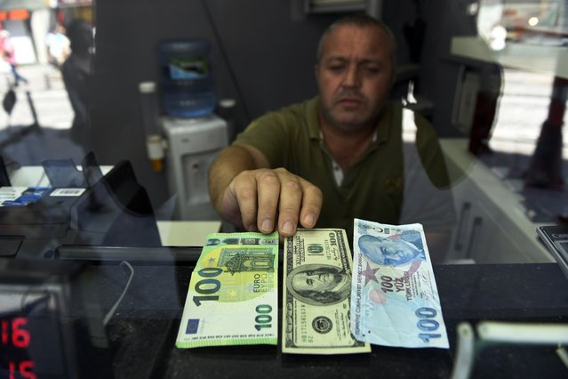 A currency exchange shop employee shows 100 Euros, 100 U.S. dollars and 100 Turkish Liras banknotes at his shop at a market street in Istanbul, Thursday, July 30, 2020. The Turkish Lira continued its trend down against the U.S. dollar Thursday but was still above a historic low in May. (Photo by Omer Kuscu/AP Photo)