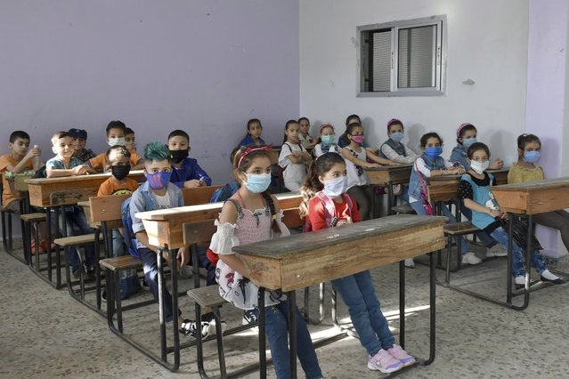 In this photo released by the Syrian official news agency SANA, students wear masks during a lesson on their first day back at school, in Hama province, Syria, Sunday, September 13, 2020. More than 3 million students went to school in government-held areas around Syria Sunday marking the first school day amid strict measures to prevent the spread of coronavirus. (Photo by SANA via AP Photo)
