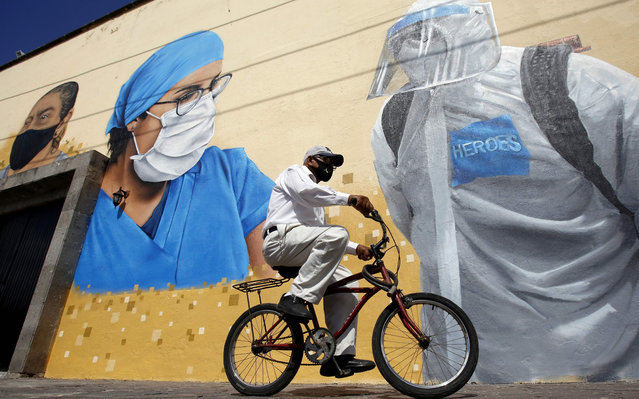 "A man rides a bicycle in front of a mural, painted by workers of the Zapopan city hall as part of the program ""Zapopart"", as a tribute to essential workers who have cared for citizens during the COVID-19 pandemic in Zapopan, state of Jalisco, Mexico, on August 12, 2020, amid the novel coronavirus pandemic. (Photo by Ulises Ruiz/AFP Photo)"