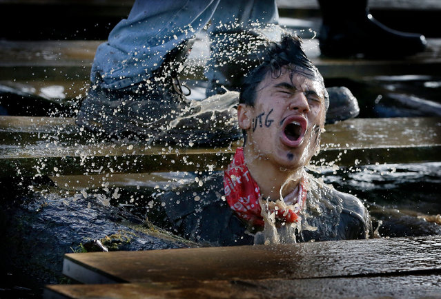 A competitor reacts during the Tough Guy Mudathon event in Perton, Britain, 04 February 2018. The original event which started in 1987 raises money for charity and challenges thousands of international competitors with a cross-country run followed by an assault course consisting of 20 obstacles including water, fire and tunnels. (Photo by  Nigel Roddis/EPA/EFE)