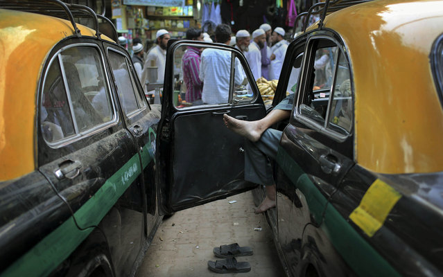 An Indian taxi driver waits for customers on a street in New Delhi, India, Thursday, March 14, 2013. (Photo by Kevin Frayer/AP Photo)