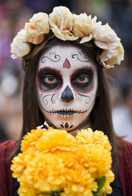 "A young girl with her face painted as a ""Catrina"" takes part in a Day of the Dead celebration in Mexico City, Sunday, October 25, 2015. The ""Catrina,"" a figure of a skeleton wearing an elegant broad-brimmed hat was first done as a satirical engraving by artist Jose Guadalupe Posada sometime between 1910 and his death in 1913. (Photo by Esteban Felix/AP Photo)"