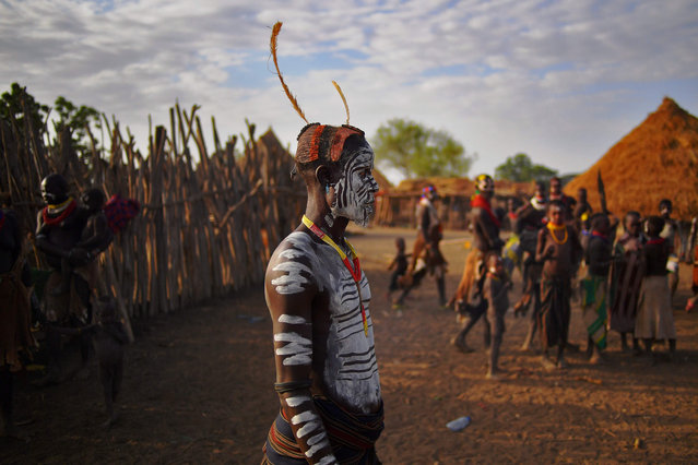 """Members of the Karo tribe pose in Ethiopia's southern Omo Valley region on September 23, 2016. The Karo are a Nilotic ethnic group in Ethiopia famous for their body painting. They are also one of the smallest tribes in the region. The construction of the Gibe III dam, the third largest hydroelectric plant in Africa, and large areas of very """"thirsty"""" cotton and sugar plantations and factories along the Omo river are impacting heavily on the lives of tribes living in the Omo Valley who depend on the river for their survival and way of life. Human rights groups fear for the future of the tribes if they are forced to scatter, give up traditional ways through loss of land or ability to keep cattle as globalisation and development increases. (Photo by Carl De Souza/AFP Photo)"""