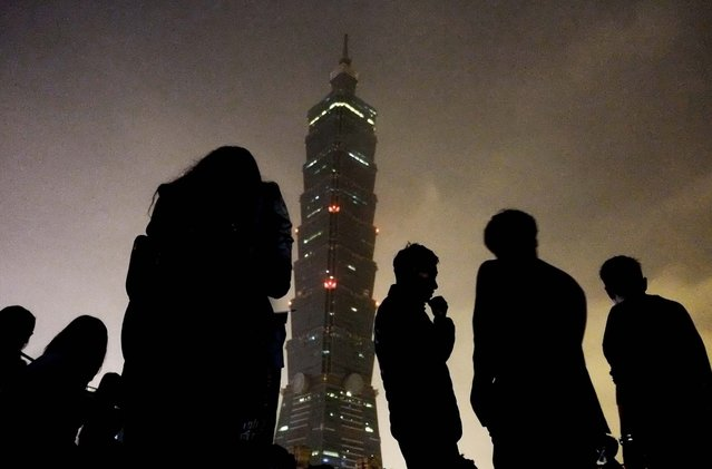 """Onlookers watch Taipei 101 building as it turns its lights off to observe international """"Earth Hour"""" in Taiwan, on March 23, 2013. Around 100 people gathered outside the skyscraper Saturday, using energy saving LED lights to observe the global event that encourages people to turn off their lights for an hour. (Photo by Wally Santana/Associated Press)"""