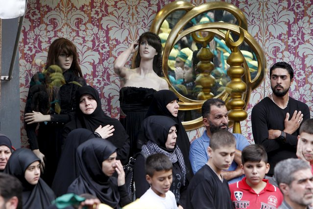 Lebanon's Hezbollah members, supporters and relatives stand near mannequins inside a shop as they attend the funeral of three Hezbollah fighters who were killed while fighting alongside Syrian army forces in Syria in Nabatieh town, southern Lebanon, October 27, 2015. (Photo by Ali Hashisho/Reuters)