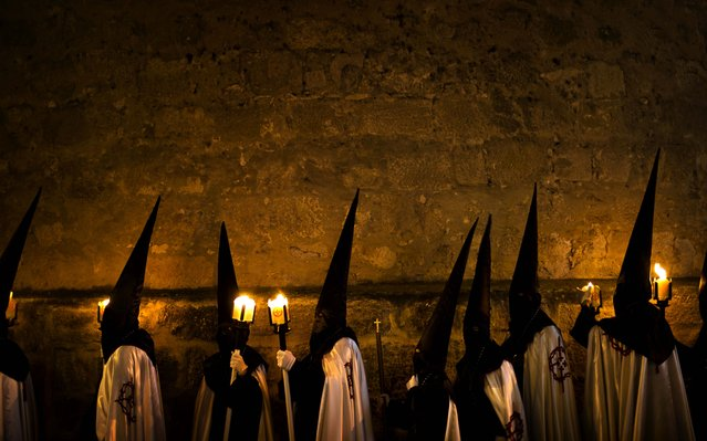 """Penitents from """"Jesus en su Tercera Caida"""" brotherhood wait in their church to take part in a procession in Zamora, Spain, on March 25, 2013.  Hundreds of processions take place throughout Spain during the Easter Holy Week. (Photo by Daniel Ochoa de Olza/Associated Press)"""