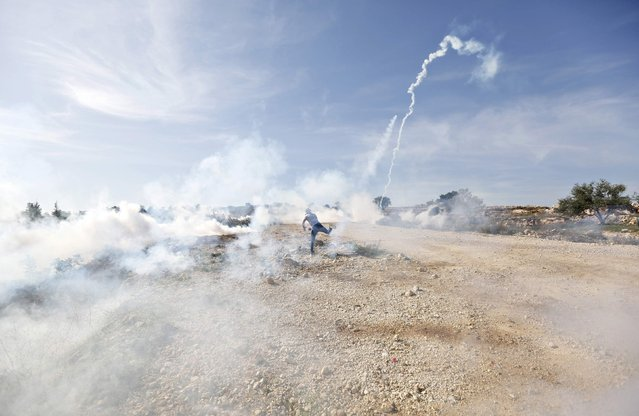 A Palestinian protester throws back a tear gas canister fired by Israeli troops during clashes following a demonstration against Jewish settlements in the West Bank village of Bilin, near Ramallah December 5, 2014. (Photo by Mohamad Torokman/Reuters)