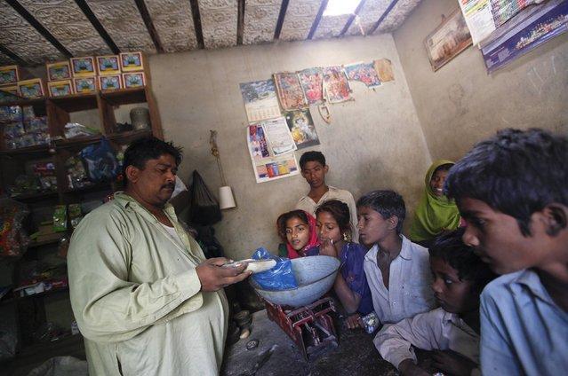 Sajan, a grocery shopkeeper weighs sugar for customers in Meeran Pur village, north of Karachi November 23, 2014. (Photo by Akhtar Soomro/Reuters)