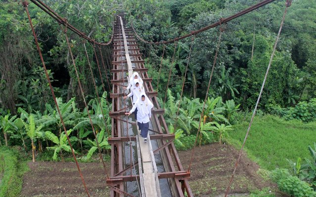 Indonesian students go to school via a makeshift suspension bridge in Ngemplak, Boyolali regency, Indonesia on November 15, 2017. The lack of access to roads makes students every day to cross the dangerous waterways to go to school. (Photo by Arief Setiadi/Pacific Press/Barcroft Images)