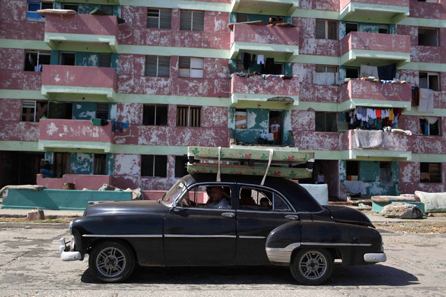 People transport beds on the roof of a vintage car after the passage of Hurricane Matthew in Baracoa, Cuba October 7, 2016. (Photo by Alexandre Meneghini/Reuters)