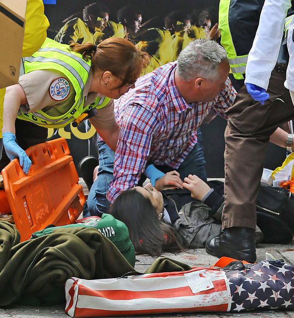 Medical workers aid injured people at the 2013 Boston Marathon following an explosion in Boston, Monday, April 15, 2013. (Photo by David L. Ryan/AP Photo/The Boston Globe)