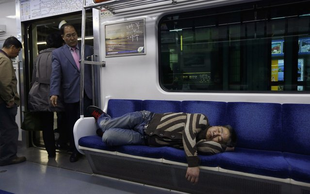 A passenger sleeps in a subway train in Seoul, South Korea Friday, April 19, 2013. (Photo by Kin Cheung/AP Photo)