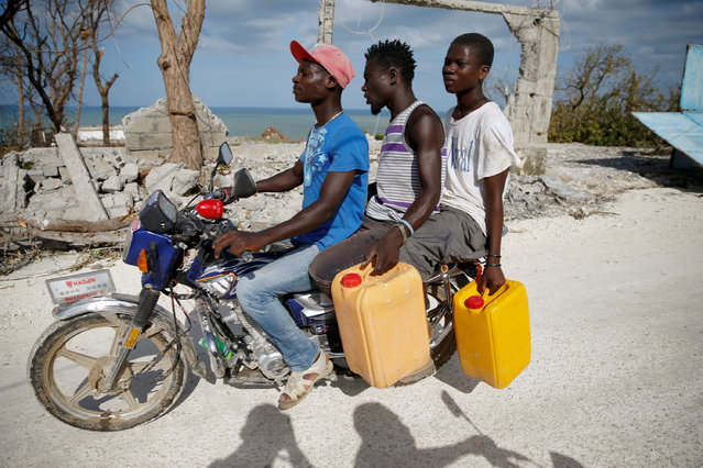 Men ride a motorcycle in front of destroyed houses after Hurricane Matthew passes Jeremie, Haiti, October 7, 2016. (Photo by Carlos Garcia Rawlins/Reuters)