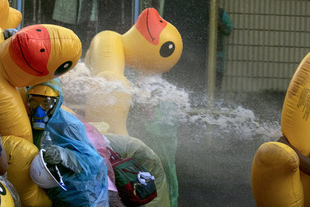 Pro-democracy protesters take cover with inflatable ducks as police fire water cannons during an anti-government rally near the Parliament in Bangkok, Tuesday, November 17, 2020. (Photo by Wason Wanichakorn/AP Photo)
