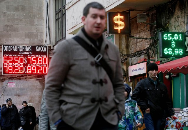 People walk past boards showing currency exchange rates in Moscow, December 17, 2014. The dramatic fall in Russia's rouble slowed on Wednesday, with the government selling foreign currency to prop it up after a 50 percent fall against the dollar this year. (Photo by Maxim Zmeyev/Reuters)