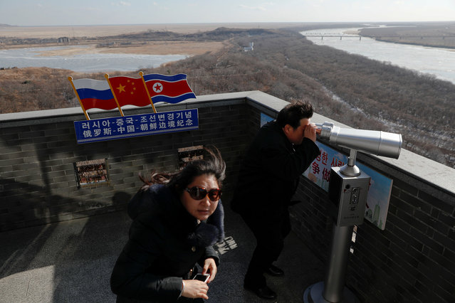 A tourist uses binoculars to look across to North Korea from a tower built on the Chinese side of the border between Russia (L), China (C) and North Korea (R) near the town of Hunchun in China, November 24, 2017. (Photo by Damir Sagolj/Reuters)