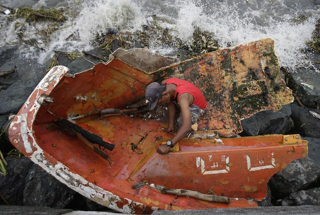 Filipino Joybin Marayo, 58, salvages metals on a damaged boat that was washed ashore by strong waves brought about by Typhoon Haima in Manila, Philippines on Thursday October 20, 2016. Several people were killed after Super Typhoon Haima smashed into the northern Philippines with ferocious wind and rains overnight, flooding towns and forcing thousands to flee then weakening Thursday after slamming into a mountain range and blowing into the South China Sea, officials said. (Photo by Aaron Favila/AP Photo)