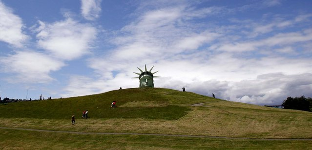 Passersby walk toward a full-scale balloon replica of the Statue of Liberty head shortly after its inflation in Seattle's Gas Works Park. (Photo by Elaine Thompson/Associated Press)