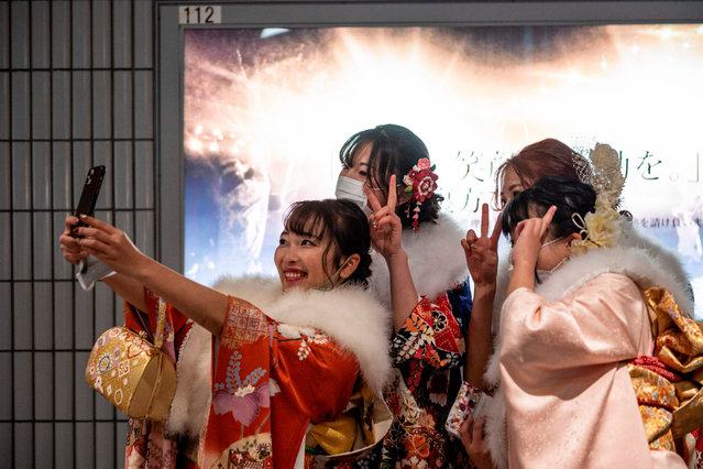 "Twenty-year-old women dressed in kimonos take pictures as they attend a ""Coming-of-Age Day"" celebration ceremony at Yokohama Arena in Yokohama on January 11, 2021 under a state of emergency over the Covid-19 coronavirus pandemic. (Photo by Philip Fong/AFP Photo)"