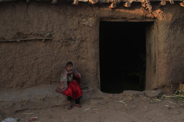 A girl sits in front of the doorway of her family dwelling in a slum in Islamabad January 6, 2015. (Photo by Faisal Mahmood/Reuters)