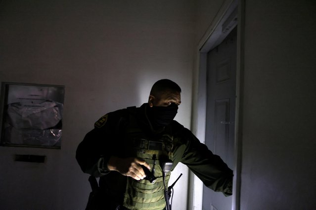 Los Angeles Sheriff's Deputy Armando Galvan searches a commercial building as he carries out an eviction, as the spread of the coronavirus disease (COVID-19) continues, in Los Angeles, California, U.S., January 13, 2021. (Photo by Lucy Nicholson/Reuters)