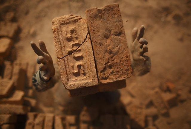 A worker stacks bricks on his head at a brick factory in Lalitpur January 12, 2015. (Photo by Navesh Chitrakar/Reuters)